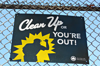 "Bord met daarop de tekst ""Clean Up or You're Out!"""