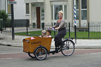 Mevrouw op een bakfiets met twee kinderen