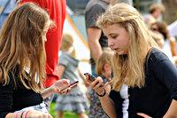 Twee jongeren met hun mobiele telefoon