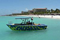 Speedboat in water voor het strand, Palm Beach, Aruba