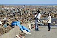 Twee volwassenen en een kind staren naar ravage van de tsunami