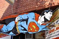 Afbeelding van vliegende superman (stripfiguur) op houten bord