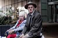 Twee oudere mensen in een rolstoel en op een rollator