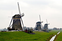 Afbeelding van drie molens op een dijk