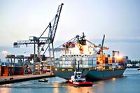 Containerschip gemanouvreerd door duwboot